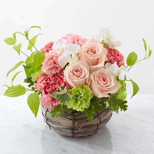 淡いピンクのバラのフラワーアレンジメントの画像